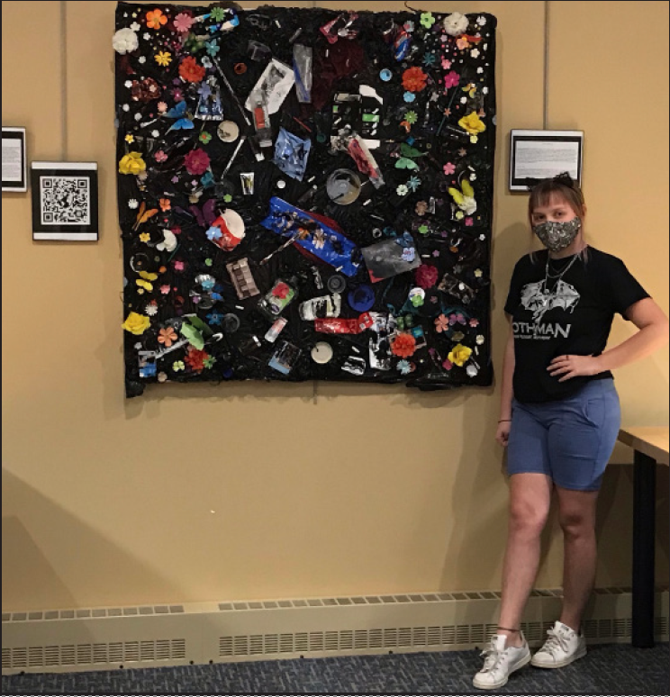 Epperly standing next to her sustainability art project on the second floor of Drinko Library.